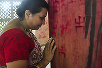 "TRIPURA, INDIA - JUNE 22: A woman prays as she draws a Holy Signs known as ""swastik"", wishing happy married life on the occasion of Ambubachi in a local temple on June 22, 2017 in Tripura, India. Ambubachi is the celebration of the menstruation of mother earth. The believe is, During Ambubachi , for three days mother earth herself menstruates. (Photo by Abhisek Saha/VIEWpress via Getty Images)"