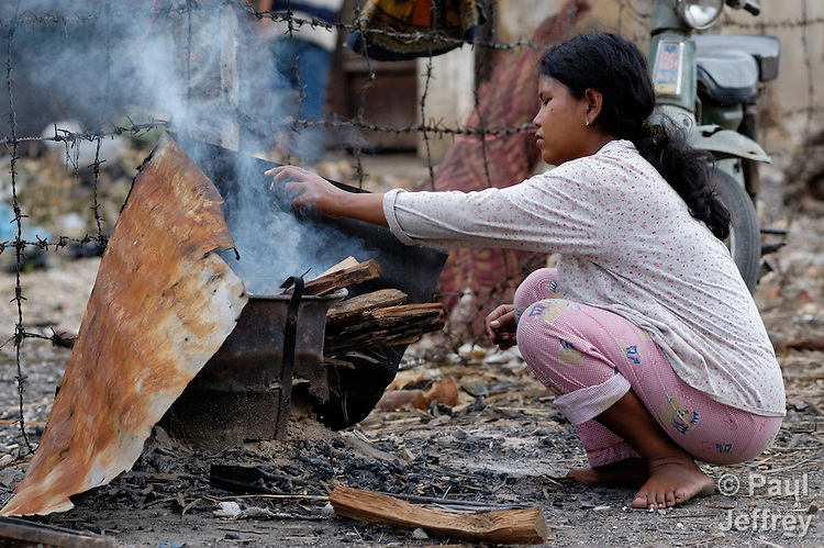 A woman in Phnom Penh, Cambodia, stokes a fire as she cooks food in a poor neighborhood.