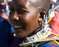A Masai girl with the traditional shaved head and wearing the traditional bead earrings and necklaces. A village near the Serengeti National Park, Tanzania.