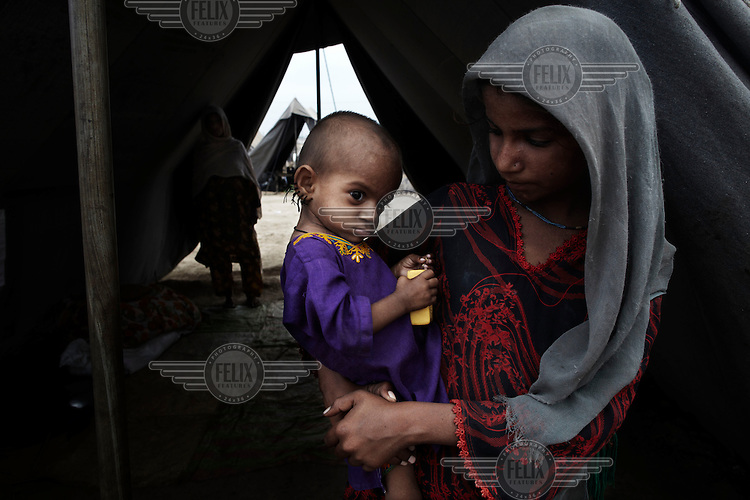 10 year old Mia Gulla holds her one year old sister Faminda at an IDP (internally displaced persons) camp set up by UNHCR (United Nations High Commission for Refugees) for those affected by the flooding. Severe flooding had left at least 1,600 people dead and affected up to 20 million.