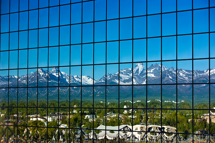 Reflection of the downtown Anchorage skyline and Chugach Mountains reflected in the glass walls of the Atwood Tower, spring foliage, Anchorage, Southcentral Alaska, USA.