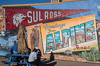 A group of locals in front of mural in Alpine Texas picnic area.