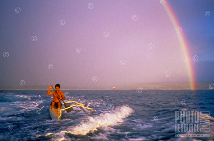 Man in outrigger canoe with rainbow