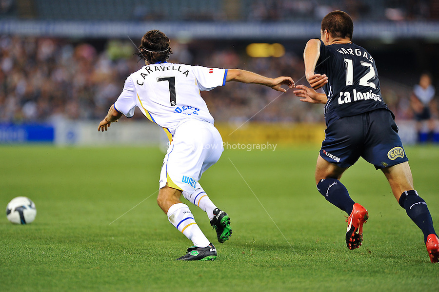 MELBOURNE, AUSTRALIA - NOVEMBER 28, 2009: Rodrigo Vargas from Melbourne Victory and Zenon Caravella chase the ball in round 16 of the A-league match between Melbourne Victory and Gold Coast United at Etihad Stadium on November 28, 2009 in Melbourne, Australia. Photo Sydney Low www.syd-low.com