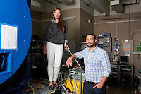 Seen here in the Space Propulsion Laboratory near a large vacuum tank, Department of Aeronautics and Astronautics Ph.D. candidates Natalya Brikner and Louis Perna (light shirt) have been working on the ion Electrospray Propulsion System (iEPS) for CubeSats at MIT in Cambridge, Massachusetts, USA.  The device is used to maneuver a 10cm cubic satellite in space. Brikner and Perna have formed a company, Accion Systems Incorporated, to commercialize the research. Brikner, graduating in Winter 2014, is CEO of the company, and Perna is co-founder. The research at MIT was done under Space Propulsion Lab director Paulo Lozano, professor in MIT's Department of Aeronautics and Astronautics.