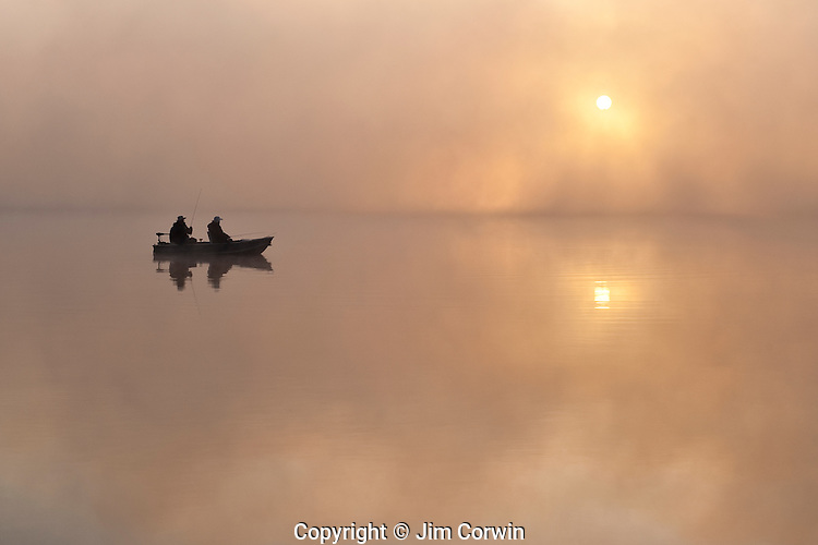 Sunrise in fog Lake Cassidy with fishermen in small fishing boat.