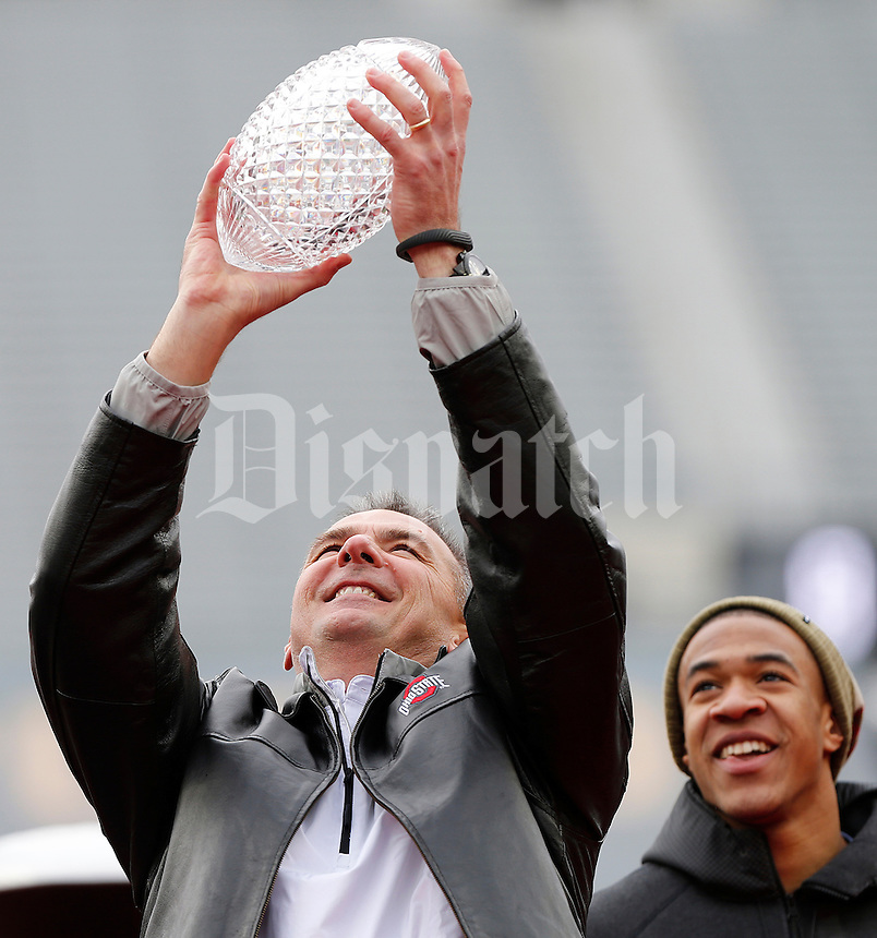 Head coach Urban Meyer holds up the Coaches Trophy as wide receiver Evan Spencer watches during the Ohio State Football National Championship Celebration at Ohio Stadium, Saturday morning, January 24, 2015. More than 40 thousand fans packed the lower stands in the stadium to celebrate the National Championship win with the football team. (The Columbus Dispatch / Eamon Queeney)