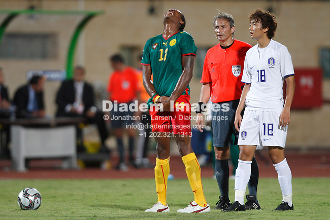 SUEZ, EGYPT - SEPTEMBER 26:  Adolphe Teikeu of Cameroon (l) reacts after being shaken up during a FIFA U-20 World Cup Group C match against South Korea September 26, 2009 at Mubarak Stadium in Suez, Egypt.  Referee Hector Baldassi (c) and Seung Yeoul Lee (r).  (Photograph by Jonathan P. Larsen)