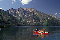 AJ3579, canoe, Grand Teton National Park, Lake Jenny, Wyoming, Grand Teton, Rocky Mountains, Grand Teton Mountains, A family paddles their red canoe on Lake Jenny with a view of the majestic Teton Mountains in front of them in Grand Teton National Park in the state of Wyoming.