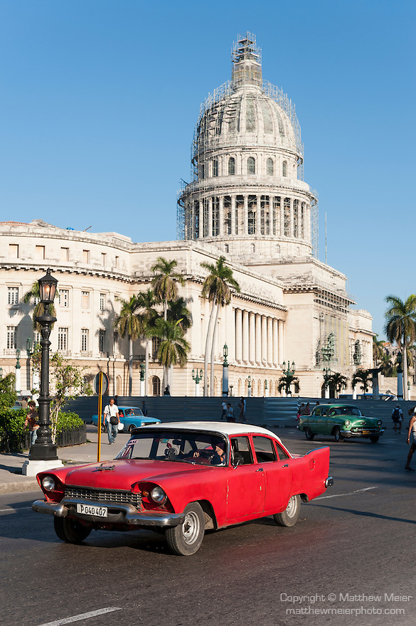 Havana, Cuba; a red and white classic 1957 Plymouth serving as a taxi during the morning commute along Paseo de Marti, with the Capitol building in the background