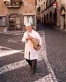 ITALY, Orvieto, Umbria, Butcher Adorno Mocetti carrying prosciutto while crossing the street.