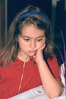 Pensive sad girl age 6 with hand on chin.  St Paul  Minnesota USA