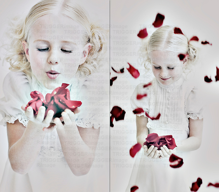 Young girl with blonde curly hair wearing white dress playing with red rose petals
