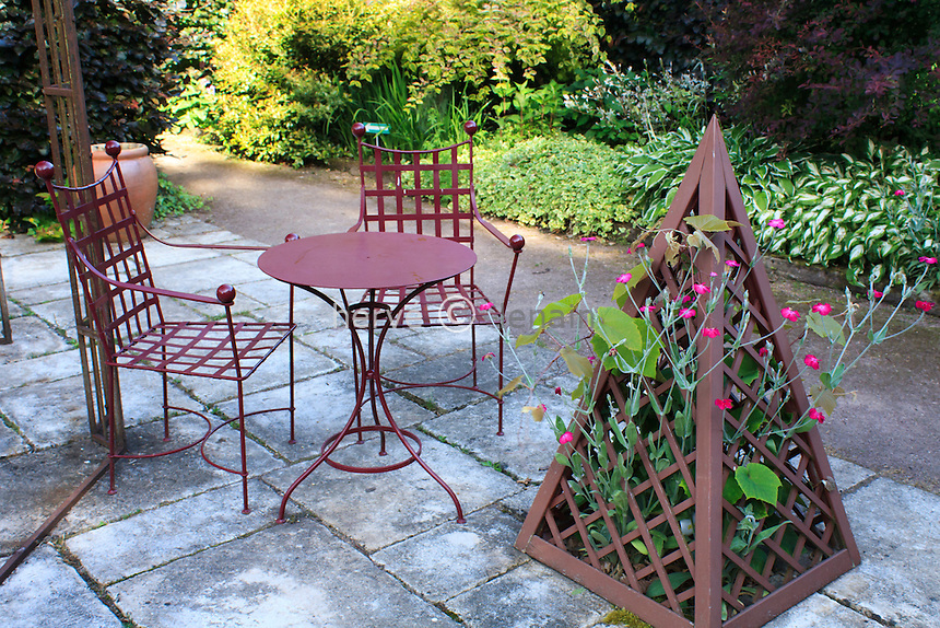 """Jardins du pays d'Auge (mention obligatoire dans la légende ou le crédit photo):.""""le jardin pourpre"""", terrasse dallée avec mobilier en fer et pyramide où pousse une coquelourde des jardins (Lychnis coronaria)."""