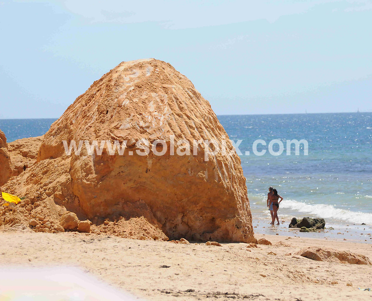 **ALL ROUND EXCLUSIVE PICTURES FROM SOLARPIX.COM**.**WORLDWIDE SYNDICATION RIGHTS**.Despite the death of five people in the rock slide on Maria Luisa beach in Albufeira, on the Algarve, Portrugal, on Friday 21st August, sunbathers return to the location to sunbathe beneath the remaining cliffs. The local town hall have substantially reduced the hight of the rock outcrop that was partially responsible for the collapse, and now removed the danger signs. The cliffs that surround the beach are still considered to be dangerous and susceptible to further rock falls..JOB REF:     9810   PPL        DATE:  26.08.09.**MUST CREDIT SOLARPIX.COM OR DOUBLE FEE WILL BE CHARGED**.**MUST AGREE FEE BEFORE ONLINE USAGE**.**CALL US ON: +34 952 811 768 or LOW RATE FROM UK 0844 617 7637**