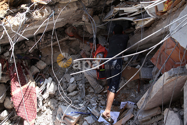 Palestinians search in the rubble of al-Qassam mosque, which witnesses said was hit by an Israeli air strike, in Nuseirat refugee camp in the central Gaza Strip on August 9, 2014. Israel launched more than 20 aerial attacks in Gaza early on Saturday and militants fired several rockets at Israel in a second day of violence since a failure to extend an Egyptian-mediated truce that halted a month long war earlier this week. The Israeli military said that since midnight it had attacked more than 20 sites in the coastal enclave where Hamas Islamists are dominant, without specifying the targets. Medical officials in Gaza said two Palestinians were killed when their motorcycle was bombed and the bodies of three others were found beneath the rubble of one of three bombed mosques. The air strikes which lasted through the night also bombed three houses, and fighter planes also strafed open areas, medical officials said. Photo by Ashraf Amra