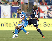Philadelphia Union defender Fabio Alves (33) dribbles as New England Revolution substitute forward Dimitry Imbongo (92) defends. In a Major League Soccer (MLS) match, the New England Revolution (dark blue) defeated Philadelphia Union (light blue), 5-1, at Gillette Stadium on August 25, 2013.