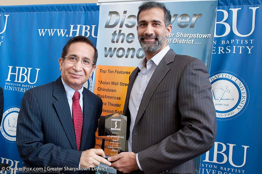 Harry Shani presents business award to AAI Affordable Housing representative, Amay Inamdar.