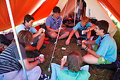 Scouts from Swtitzerland is playing cards in a tent. Photo: Magnus Fröderberg/Scouterna