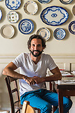 PORTUGAL, Lisbon, Portrait of Chef Jose Avillez sitting in his restaurant Cantinho do Avillez. Blue China plates in the background