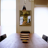 A 1950's style poster graces a wall of the dining room which has a Serge Mouille pendant light above the wooden table