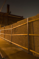 Williamsburg, Brooklyn -Mysterious Cityscape at Night....The landmarked 1884 Domino Sugar Refinery, sidewalk and construction site fence.