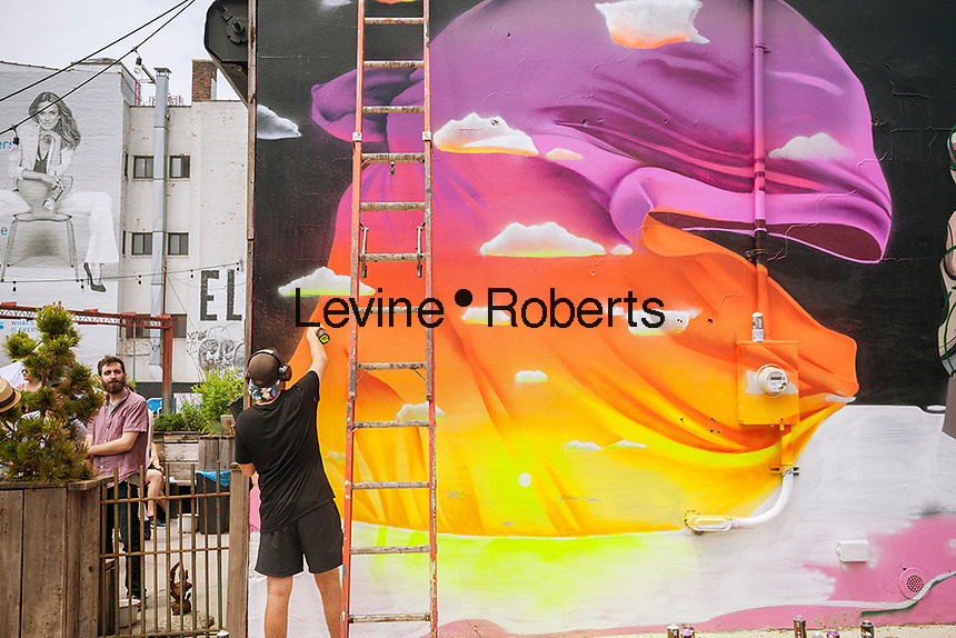 """Buff Monster works on his mural in Bushwick, Brooklyn in New York during the annual Bushwick Collective Block Party on Saturday, June 4, 2016. Music and partying brought some but the real attraction was the new murals  by """"graffiti"""" artists that decorate the walls of the buildings that the collective uses.  (©Richard B. Levine)"""
