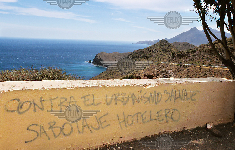 Anti-construction graffiti protesting against the increasing tourist-centred urbanisation of the area is painted onto a wall along the Cabo de Gata nature reserve coastline. In recent years there has been an explosion of controversial tourist-focused developments in Spain's arid southeastern region causing environmental degradation and placing enormous pressure on the limited amenities in the area.