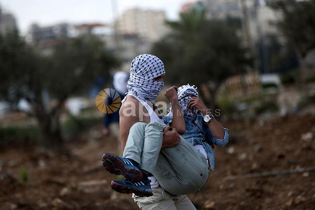 A Palestinian protester is evacuated by comrades after being injured during clashes with Israeli security forces in Beit El on the outskirts of the West Bank city of Ramallah, on October 10, 2015. Fifteen Palestinians have been killed by Israeli forces and around 1,000 injured with live and rubber-coated steel bullets in the occupied West Bank and Gaza Strip since Oct. 1. Photo by Shadi Hatem