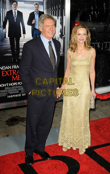 "HARRISON FORD & CALISTA FLOCKHART.arriving at the premiere of ""Extraordinary Measures"" at Grauman's Chinese Theatre in Hollywood, California, USA,   January 19th, 2010..arrivals full length suit  blue shirt tie navy black polka dot holding hands hand in pocket gold crochet dress sleeveless long maxi sandals clutch bag couple .CAP/ROT.©Lee Roth/Capital Pictures"