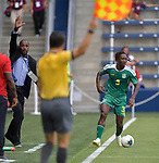 Trinidad and Tobago head coach Dennis Lawrence (left) raises his hand just as the sideline official calls the ball out of bounds on Daniel Kadell (3) of Guyana during a Gold Cup match against Trinidad and Tobago on June 26, 2019 at Children's Mercy Park in Kansas City, KS.<br /> Tim VIZER/AFP