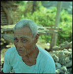 An old balinese farmer sits by the sea.