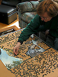 Woman working on jig saw puzzle