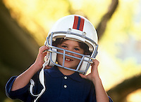 Young boy tests out a football helmet.