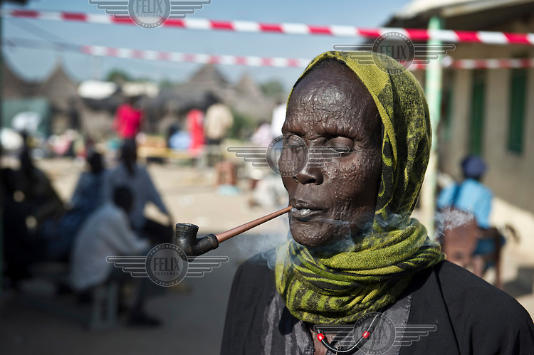 An elderly woman with scarification marks smokes next to a referendum centre where people can register themselves for the upcoming referendum on independence. Together with many other IDPs (Internally Displaced Persons) she has just returned from Khartoum, the capital in the north, to South Sudan. Many Sudanese, who fled Sudan during the civil war, are returning home, mainly to participate in the upcoming referendum in January 2011, when South Sudan will vote on its independence.
