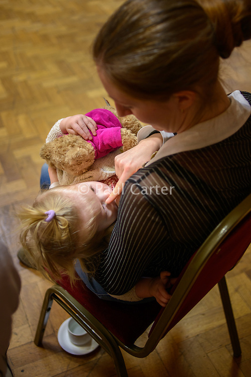 "A mother breastfeeding her toddler at a conference.<br /> <br /> Image from the breastfeeding collection of the ""We Do It In Public"" documentary photography picture library project: <br />  www.breastfeedinginpublic.co.uk<br /> <br /> <br /> Middlesex, England, UK<br /> 2016<br /> <br /> © Paul Carter / wdiip.co.uk"