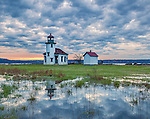 Vashon-Maury Island, WA: Point Robinson Lighthouse reflecting in a small pond at sunrsie with storm clouds