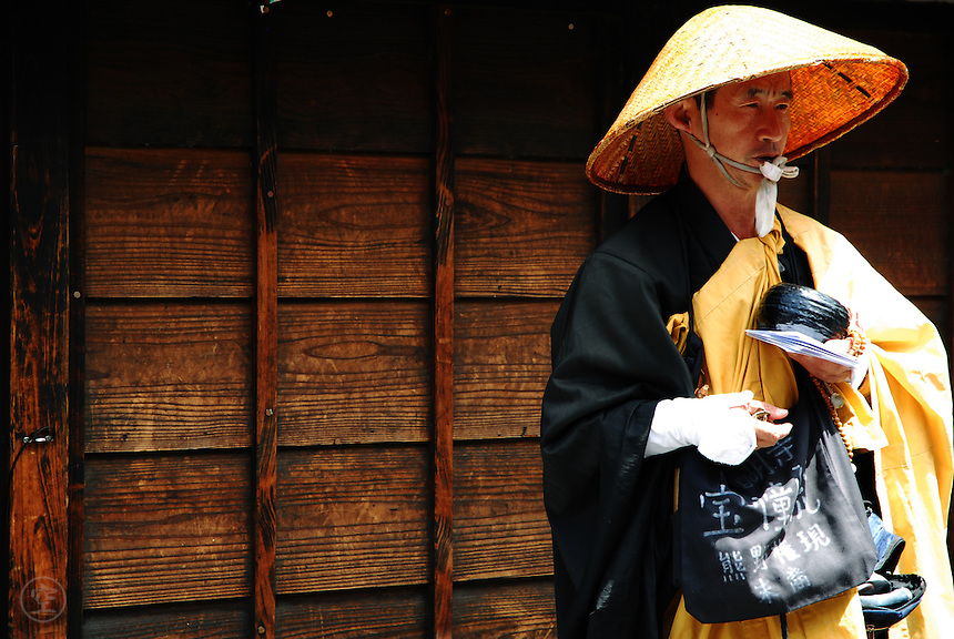 A Buddhist monk begs for alms along a street below Kiyomizu Temple in Kyoto, Japan