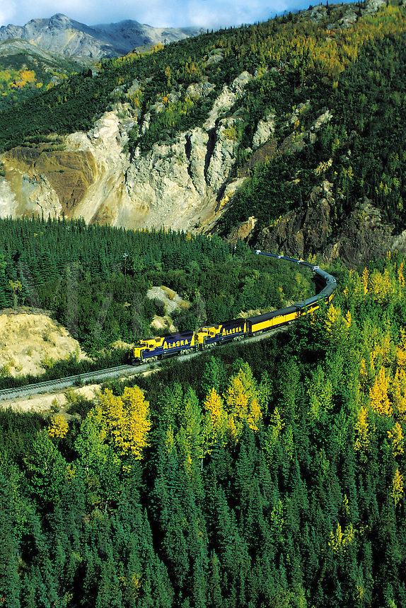 Aerial view of a passenger train traveling through a forest mountain pass in autumn. Alaska.