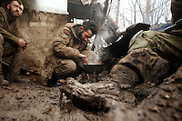 "UKRAINE, 02.2016, Oblast Donetsk. Ukrainian-Russian conflict concerning Eastern Ukraine / Foreign volunteers (""Task Force Pluto"") fighting with the far-right militia Pravyi Sektor against the Russian-backed separatists: Ben and Alex from Austria prepare a meal on the camp fire in their muddy trench at the Donetsk frontline. © Timo Vogt/EST&OST"