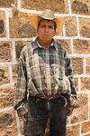 Portrait of Guatemalan man with cowboy hat in front of church wall in San Juan La Laguna, Lake Atitlan, Guatemala