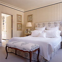 The guest bedroom is themed with blue and white from the striped fabric which lines the walls to the Ralph Lauren fabric on the bed