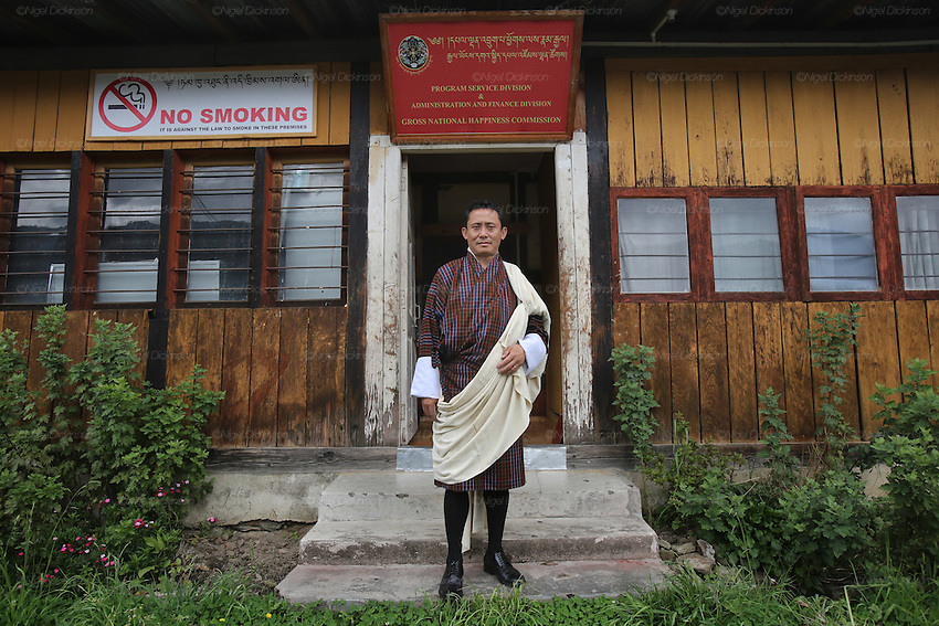 "The minister of ""Gross National Happiness"" stands outside his parlimentary office in the grounds of the Government Dzong. Thimpu..Bhutan the country that prides itself on the development of 'Gross National Happiness' rather than GNP. This attitude pervades education, government, proclamations by royalty and politicians alike, and in the daily life of Bhutanese people. Strong adherence and respect for a royal family and Buddhism, mean the people generally follow what they are told and taught. There are of course contradictions between the modern and tradional world more often seen in urban rather than rural contexts. Phallic images of huge penises adorn the traditional homes, surrounded by animal spirits; Gross National Penis. Slow development, and fending off the modern world, television only introduced ten years ago, the lack of intrusive tourism, as tourists need to pay a daily minimum entry of $250, ecotourism for the rich, leaves a relatively unworldly populace, but with very high literacy, good health service and payments to peasants to not kill wild animals, or misuse forest, enables sustainable development and protects the country's natural heritage. Whilst various hydro-electric schemes, cash crops including apples, pull in import revenue, and Bhutan is helped with aid from the international community. Its population is only a meagre 700,000. Indian and Nepalese workers carry out the menial road and construction work."
