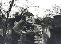 A woman in Jusici, Bosnia clears off debris from what's left of her home to prepare it for rebuilding. Serbs burned the village during the war.