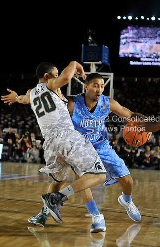 University of North Carolina guard Kendall Marshall (#5) drives the ball against Michigan State guard Travis Trice (#20) Friday, November 11, 2011 during the Quicken Loans Carrier Classic basketball game aboard the Nimitz-class aircraft carrier USS Carl Vinson (CVN 70) in San Diego, California. The inaugural Carrier Classic is a celebration of Veterans Day..Mandatory Credit: Roza Arzola - U.S. Navy via CNP