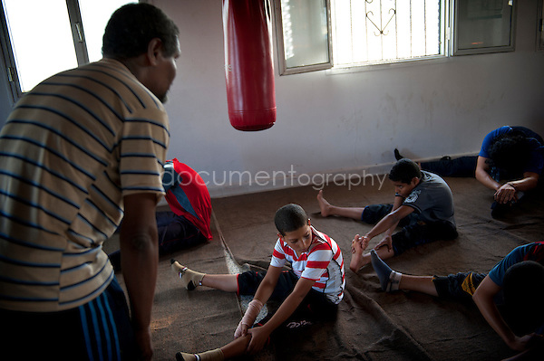 For the warm-up session, two big carpets are unwound to welcome the young sportsmen. Sitting cross-legged, they do not escape the rite of stretchings. Abdel Salam, a former boxer, is one of the 2 coaches of the club. His pride: to train Ahmed, his 10-year-old son.