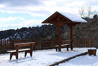 A wooden bench and a shade near a railing on the edge of a valley at Troodos mountain after snow-fall.