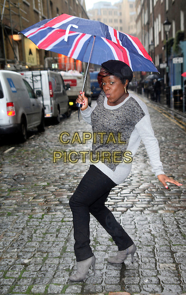 Tameka Empson.photocall ahead of the 10th anniversary performance of 'Our House', London, England, UK, October 19th, 2012..full length grey gray top jeans  union jack umbrella raining funny jumper hat cap .CAP/JEZ  .©Jez/Capital Pictures.