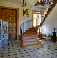 The dramatic entrance hall is dominated by a sweeping curved staircase