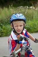 Winking Polish bicycler boy age 8 wearing a helmet. Zawady Central Poland
